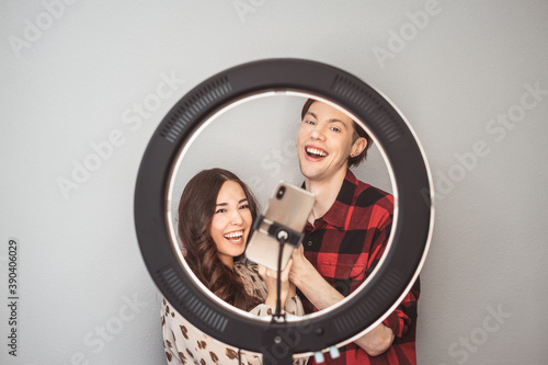 Young couple of beauty bloggers, hair stylist, hairdresser and model with hair style shoot on mobile phone with ring lamp on the grey wall background