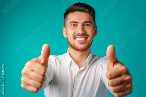 Obraz Positive handsome hispanic businessman showing thumb up gesture - fototapety do salonu