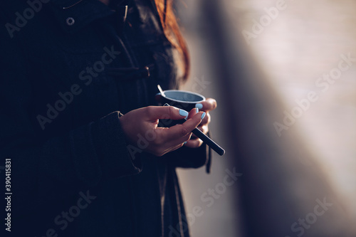 Fototapeta Young woman smoking vape cig and drinking instant coffee beverage outdoor