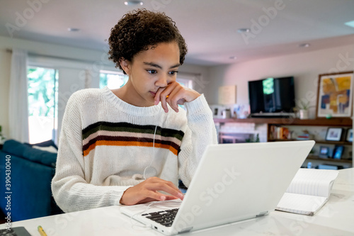 Teen girl doing remote school from home on laptop computer in kitchen Fototapet