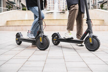 Cropped Shot Of Electric Scooters With Legs On Them Outdors