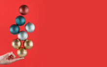 Person Holding With One Finger Brightly Colored Christmas Spheres Striking A Balance On A Red Background With Copy Space. Christmas Decorations. Christmas Wallpaper