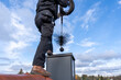 Leinwandbild Motiv Chimney sweep cleaning a chimney standing on the house roof, lowering equipment down the flue