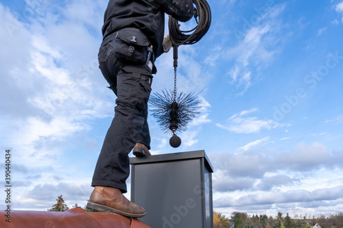 Chimney sweep cleaning a chimney standing on the house roof, lowering equipment Fototapet