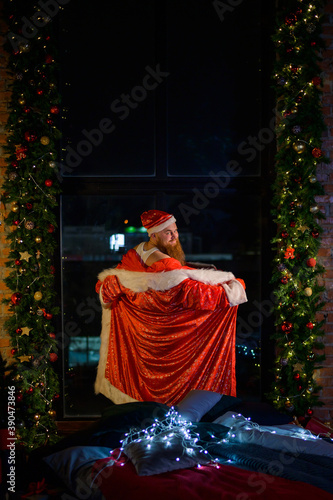 Fototapeta Bad evil Santa Claus opened his robe in front of the window on Christmas Eve
