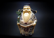 Purchased Ceramic Figurine Of A Chinese Old Man Close Up On A Black Background