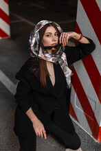 Fashionable Young Woman Model In Stylish Elegant Clothes Takes Off Sunglasses And Looks At The Camera. Cute Girl In Seasonal Wear With Silk Scarf On Head Sits Near Vintage Striped Column On The Street
