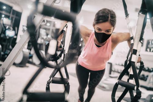Fototapeta premium Woman training at gym wearing face mask for Coronavirus prevention while exercising strength indoors.