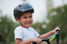 A Four Year Old Boy Smiles, While Wearing His Bicycle Helmet For Safety And Holding On To The Bike's Handle Bars.