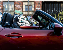 Red Sports Car Front Seats Side View With Graffiti Urban Backdrop