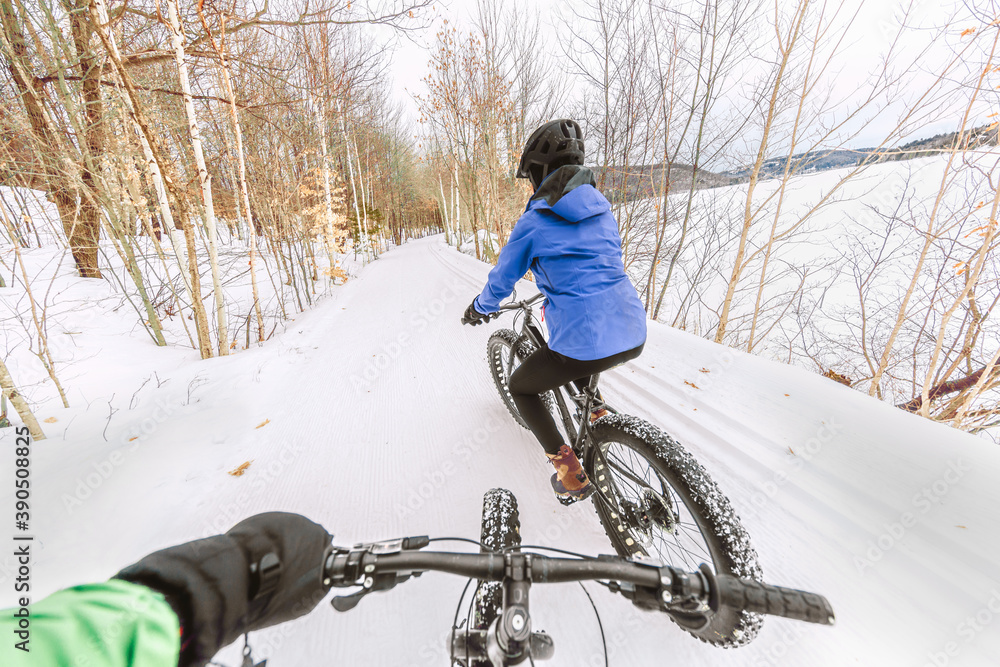 Fototapeta Couple biking on fat bikes on winter snow trail outdoor. Mountain nature landscape, woman rider cycling from behind with point of view of man holding handlebar of his bike.