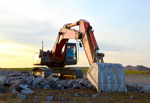 Excavator On Destruction Of Concrete And Hard Rock At The Construction Site. Recycling Concrete Waste In Mobile Jaw Crusher Machine At Landfill.  Heavy Construction Equipment And Machinery