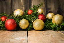 Christmas Background With Green Branches And Christmas Balls On The Rustic Wooden Background. Selective Focus. Shallow Depth Of Field.