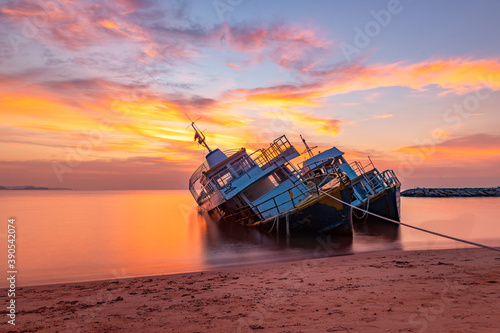 Older shipwreck or abandon transportation boat parking on beach with beautiful sunset and twilight sky Fototapet