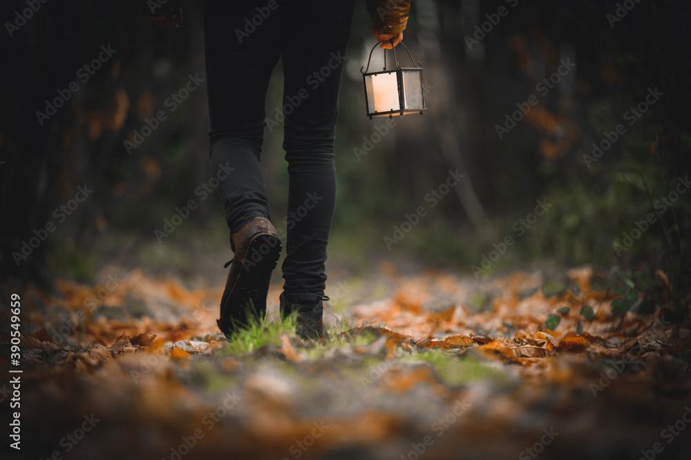 Fototapeta Man walking with a lantern in a woods