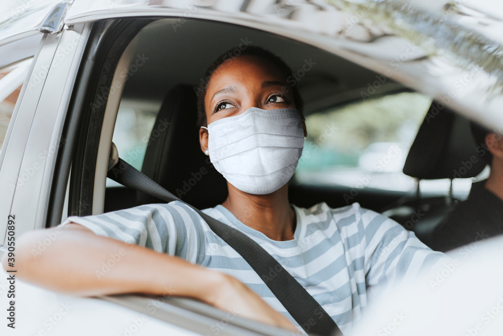 Fototapeta Woman with mask at drive thru with her car