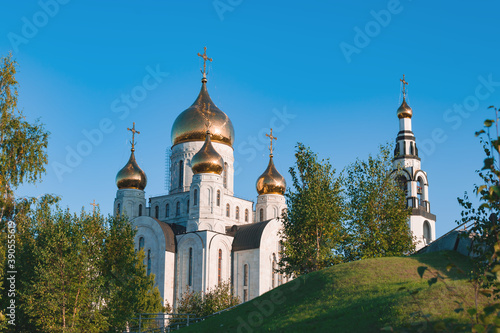 Fotografiet Orthodox Church made of white stone with Golden domes among green trees against a blue sky