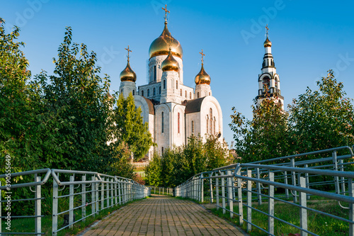 Fotografie, Tablou Orthodox Church made of white stone with Golden domes among green trees against a blue sky