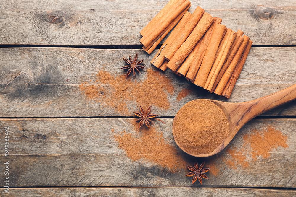 Obraz Spoon with cinnamon powder and sticks on wooden background fototapeta, plakat