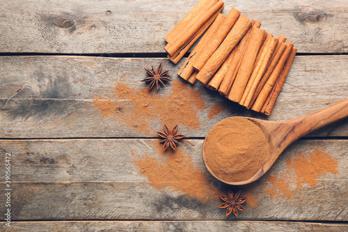 Fototapeta Spoon with cinnamon powder and sticks on wooden background obraz