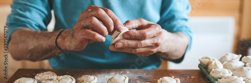 Fototapeta hands of senior man cooking and molding small homemade uncooked dumplings with meat on kitchen table. national traditional Russian cuisine. do it yourself. banner obraz
