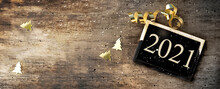 2021 Writing On A Little Board On Rustic Wooden Background With Golden Confetti And Ribbon