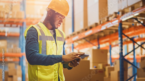 Male Worker Wearing Hard Hat Checks Products Stock and Inventory with Digital Tablet Standing in Retail Warehouse full of Shelves with Goods. Distribution, Logistics.