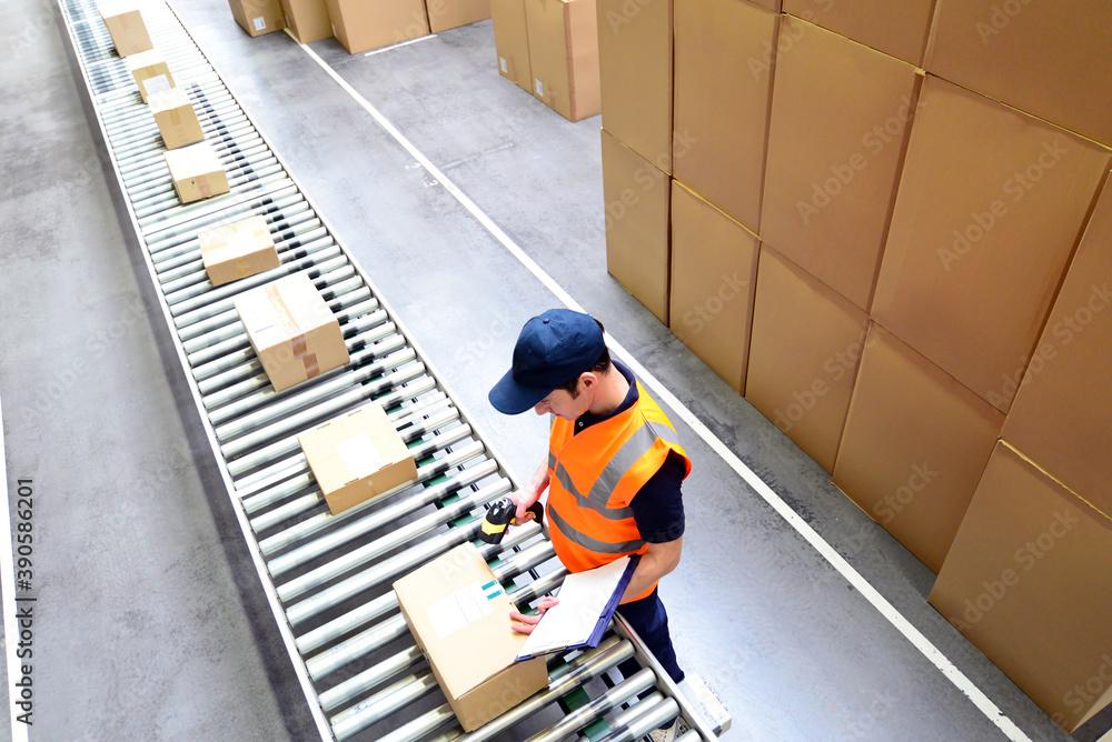 Fototapeta Mann scannt Pakete für den Versand im Versandhandel ein - Fliessband mit Paketen // Man scans parcels for mail order dispatch - assembly line with parcels