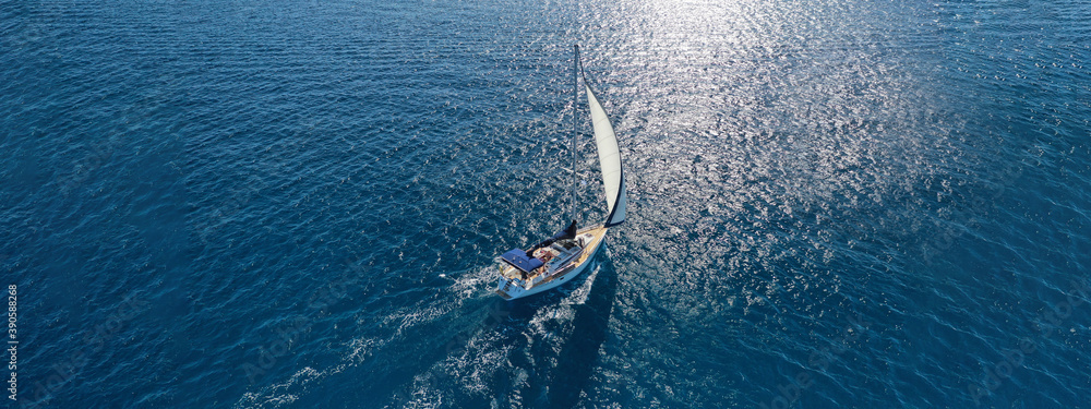 Fototapeta Aerial drone ultra wide photo of beautiful sailboat sailing in tropical exotic bay with emerald clear sea