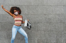 Young Afro Woman Wearing Face Mask Dancing Outdoor While Listening To Music With Wireless Headphones And Vintage Boombox Stereo