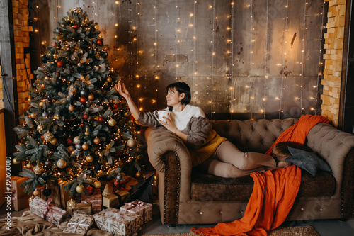 Fotografie, Obraz Woman sitting on sofa with a cup of coffee or tea next to a Christmas tree at home