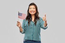 Independence Day, Patriotism And National People Concept - Happy Asian Woman With Flag Of America Showing Thumbs Up Over Grey Background