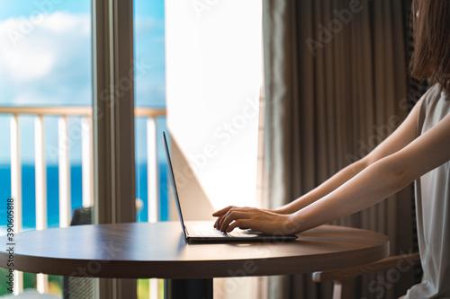 Carta da parati 海が見えるホテルで仕事する女性