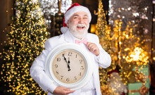 Happy New Year. Wait For Xmas Presents. Santa Man Hold Alarm Clock. New Year Midnight. Clock Showing Almost Midnight. Time To Celebrate Winter Holidays. Hurry Up. Christmas Countdown Arriving