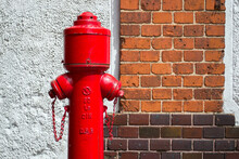Old Red Fire Hydrant Against The Brick Wall