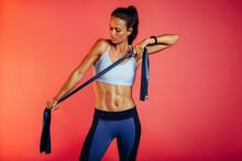 Female Athlete Using Resistance Band For Training