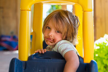 Portrait Of Smiling 4 Year Old Boy With Chocolate On His Face Playing With Older Sister