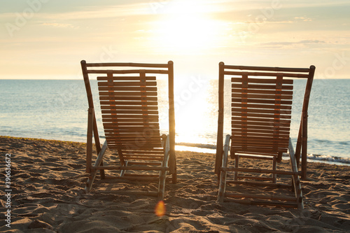 Photo Wooden deck chairs on sandy beach at sunset. Summer vacation