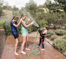 Children Spraying Each Other With Water Hose