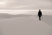 Man In A Black Coat And Suit, A Bowler Hat And Umbrella, In A White Desert Wilderness Of White Sand.