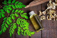 Oil Of Moringa In Bottle, Green Leaves, Pods And Seeds On Wooden Background. Moringa Oleifera Tropical Herb Product Concept.