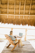 Young Man Using A Laptop Underneath Thatch Roof On The Beach