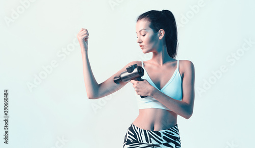 Athletic young female massaging hand by handheld massage gun, post-workout recovery routines