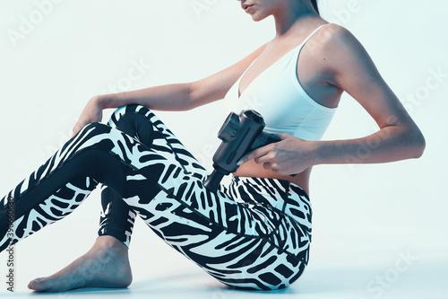 Obraz Sports young girl in sportswear massaging leg by massage gun in studio, pre-workout warm-ups, close up cropped ad photo - fototapety do salonu