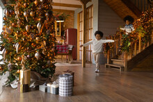 Overjoyed African American Little Kids Wearing Sweaters Running Downstairs On Christmas Morning To Opening Presents, Gift Boxes Under Decorated Festive Tree, Excited Girl And Boy Celebrating New Year