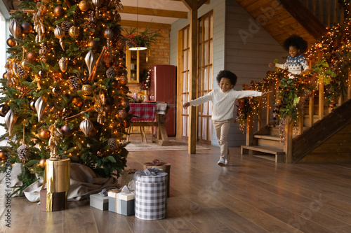 Obraz Overjoyed African American little kids wearing sweaters running downstairs on Christmas morning to opening presents, gift boxes under decorated festive tree, excited girl and boy celebrating New Year - fototapety do salonu