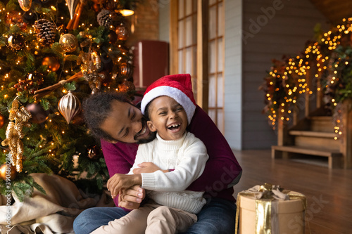 Fototapeta Overjoyed African American man hugging adorable little son wearing festive red cap, family celebrating Christmas, opening gifts, sitting on warm floor at home near tree, enjoying winter holidays obraz