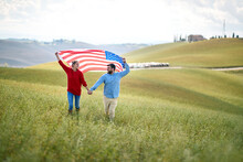 A Couple In Love Running Through A Meadow With Unfurled American Flag Holding By Hands. Election, Campaign, Freedom Concept