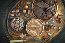 Pieces Of Dark Chocolate And Cocoa Beans In Composition On Old Background