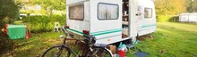 Caravan Trailer With A Bicycle Parked On A Green Lawn Under The Trees In A Camping Site. France. Vacations, Leisure Activity, Tourism, Road Trip, Travel Destinations, Lifestyle. Panoramic View